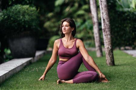 Woman practicing yoga performing yoga-asanas outdoors.