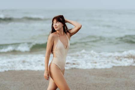 woman in bikini posing behind blue ocean