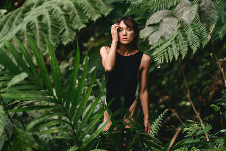 Attractive young woman among the tropical plants.