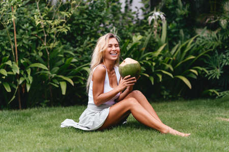 Beautiful blonde woman in the white dress on the tropical terrace with coconut