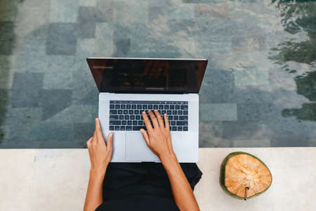 Woman freelance work typing on laptop with fresh coconut .