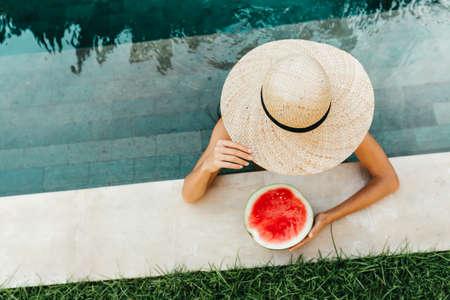 Girl holding watermelon in the blue pool, slim legs