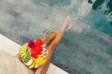 Girl relaxing and eating fruit plate by the hotel pool. Exotic summer diet.