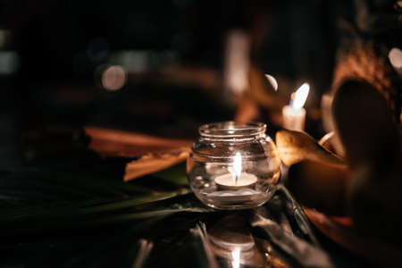 A candle in a glass vase, decoration and various interesting elements on a dark wooden background. Standard-Bild