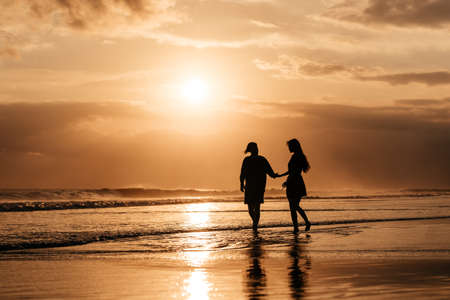 Attractive man and woman enjoying romantic evening on sunset