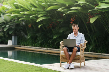 Young man using a laptop computer in a garden with a swimming pool.