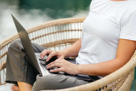 Young woman near swimming pool and working at latop computer