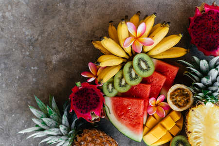 Tropical fruits assortment on a wooden plate. Stone background.