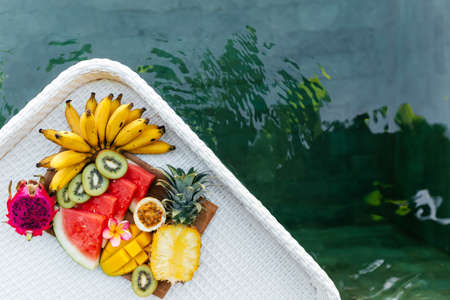 Still life image of tropical fruits and flowers near the pool