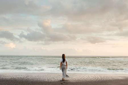 Happy Woman Enjoying Beautiful Sunset on the Beach