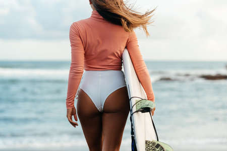 Young attractive surfer woman with white board at sunset on the ocean. Bali Indonesia.