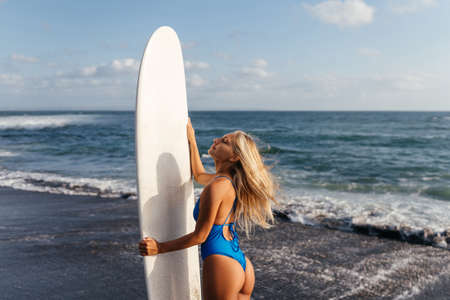 Surfer woman with board on the sandy beach, water sports.