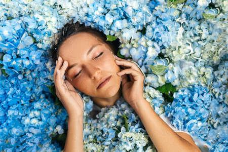 Woman relaxing in bath with tropical blue hydrangea. 版權商用圖片