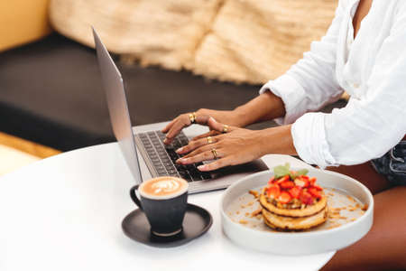 women hands at table with laptop near delicious pancakes with berries