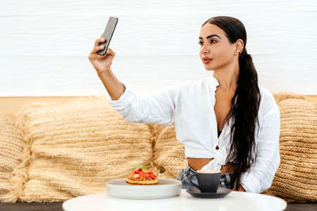 Beautiful young woman with mobile phone eating tasty pancake in cafe