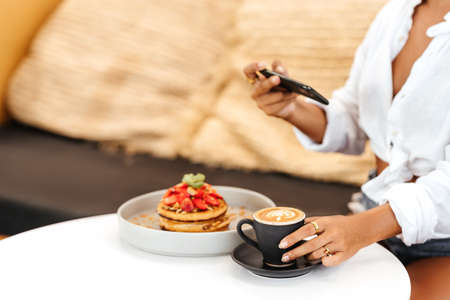 Woman taking a photo of breakfast with smartphone 版權商用圖片