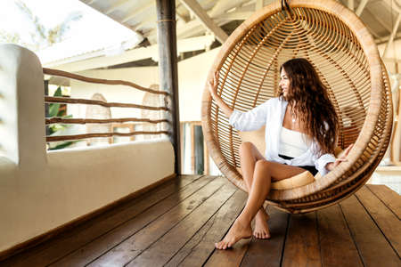 Stylish young brunette woman siting in round hanging chair.