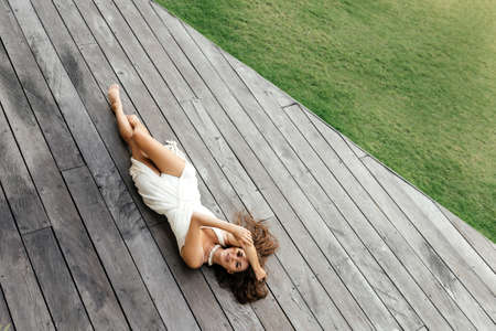 Photo of beautiful lady in white dress laying on the wooden floor,summer accessories.