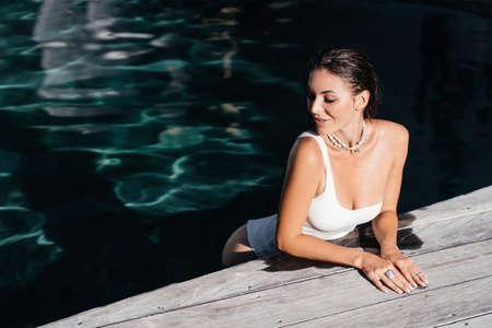 beautiful long hair female model posing by the pool, outdoor portrait 版權商用圖片