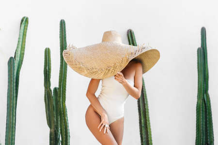 Portrait of a slim young woman in front of a cactus wall.