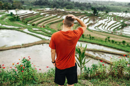Young happy tourist enjoying the lovely view of the rice terrace in Bali, Indonesia.