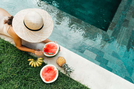 Young attractive woman at the pool enjoying delicious ripe tropical fruits: watermelon, bananas and pineapple. 版權商用圖片