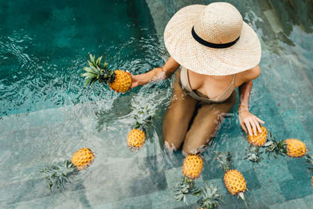 Young attractive woman by the pool enjoying delicious ripe tropical pineapple.