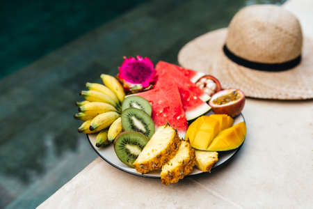 A plate of tropical fruits: watermelon, pineapple, bananas, mangosteen, passion fruit, mango and dragon fruit.