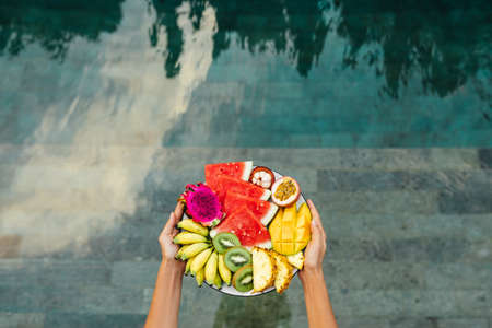 Young unrecognizable woman by the pool with a plate of tropical fruits: watermelon, pineapple, bananas, mangosteen, passion fruit, mango and dragon fruit.