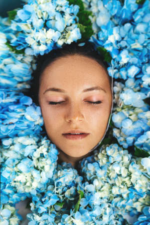 Woman relaxing in bath with tropical blue hydrangea. Imagens