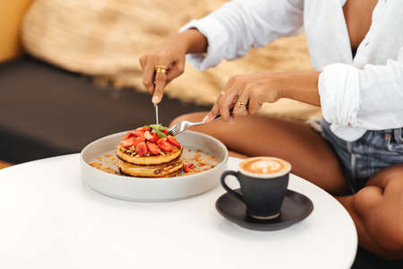 Beautiful young woman eating pancakes in a cafe Imagens