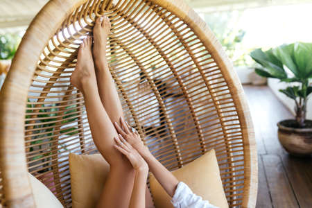 legs of woman in the rattan lounge hanging chair at the balcony