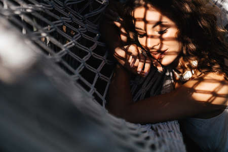 Attractive young woman is relaxing outdoor while lying in hammock.