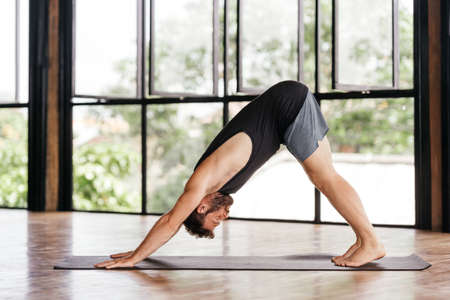 Yoga men workout in studio in front of a window