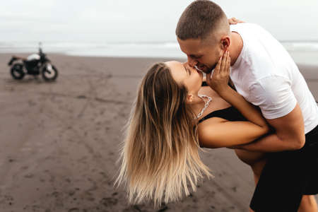 Young couple riders together on sand beach by motorbike Imagens