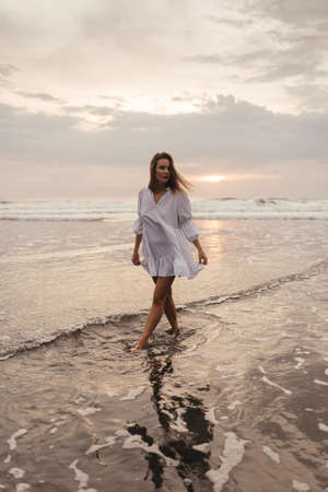 young woman wearing beautiful white dress is walking on the beach during sunset Imagens