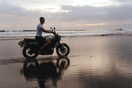 Surfer rides on motorbike with surfboard at sunset ocean beach.