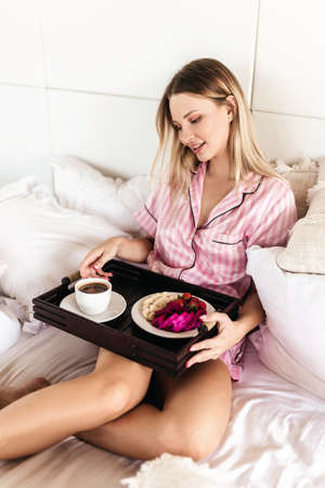 Young woman working at home in the bedroom during morning breakfast
