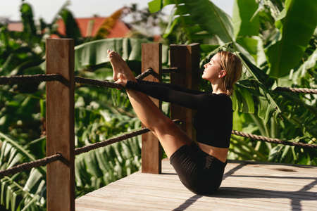 Woman doing stretching exercises outdoors in the morning.