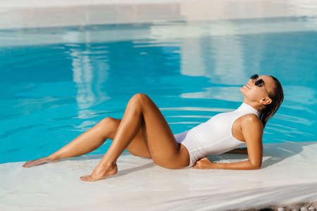 Young woman relaxing in swimming pool on summer vacation. Imagens