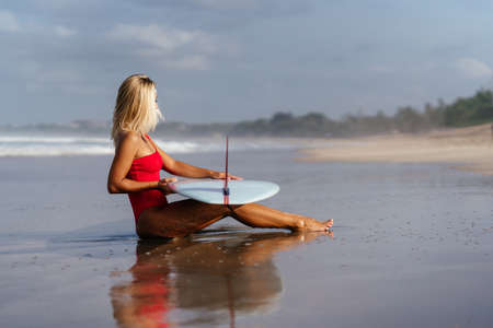 Surf woman with long blonde hair go to ocean.
