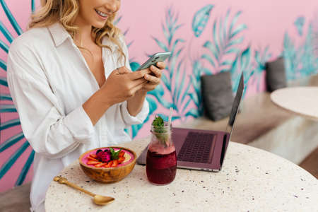 Young woman using smartphone and laptop outside a cafe