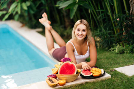 Woman relaxing and eating fruits in the pool on luxury villa in Bali.