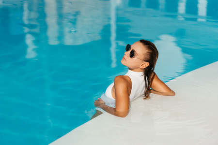 Young woman relaxing in swimming pool on summer vacation. Фото со стока