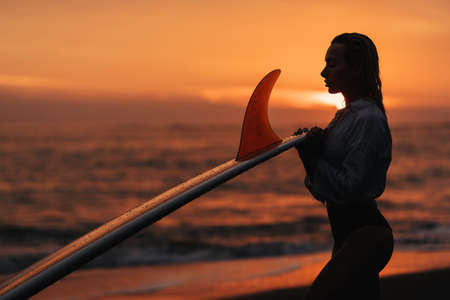 woman on tropical beach holding surfboard at sunset