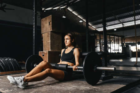 Fit young woman at a crossfit style on dark gray background.