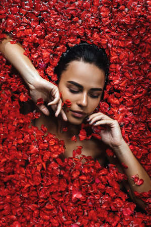 Close-up, top view, beauty portrait, face of a young woman in a bath with water and floating red rose petals and rosebuds.