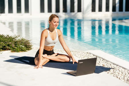 Young fit woman doing yoga stretching exercise outdoor near swimming pool in front of laptop.