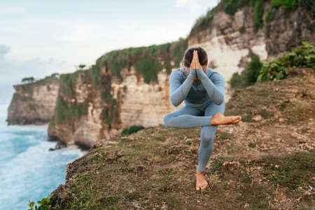 Beautiful woman doing yoga on a cliff, behind an amazing view in the ocean