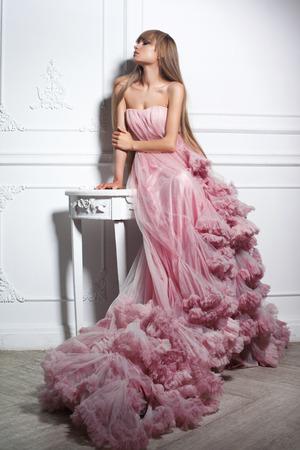 Ritratto di una donna di moda in abito rosa lungo splendido